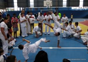 Grupo de capoeira se apresenta durante reinauguração de quadra.