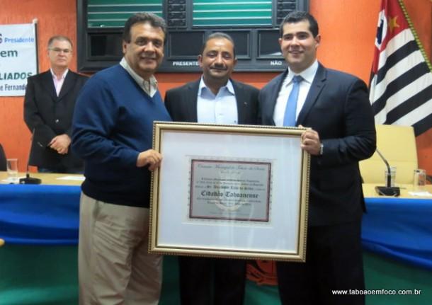 Prefeito Fernando Fernandes e o vereador Cido  entregam o título de 'Cidadão Taboanense' ao deputado federal Alexandre Leite.