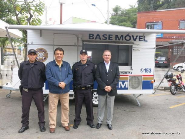 Prefeito Fernando Fernandes e secretário Gerson Brito posam ao lado de guardas em frente a base móvel.