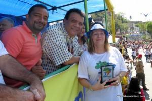 Ao centro, o prefeito Fernando Fernandes e o vereador Cido entregam troféu de participação a diretora Carmen da EMEF Ugo Arduini.