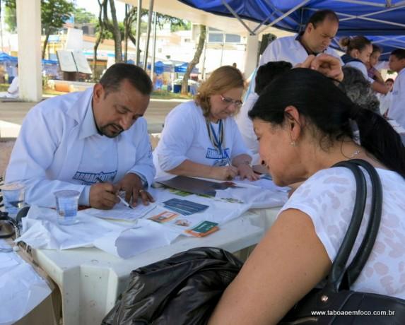 Vereador Cido, que também é farmacêutico, orienta mulher durante evento em Taboão da Serra.
