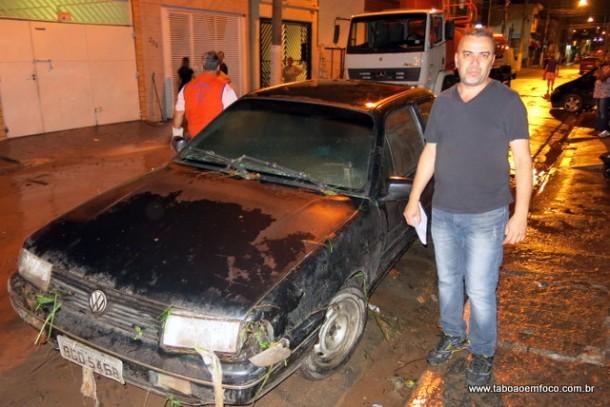 Morador de Taboão mostra carro danificado pela enchente.