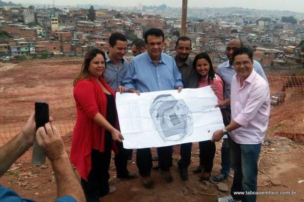Ao lado de vereadores, prefeito Fernando segura a planta da futura Arena no Jd. Record.