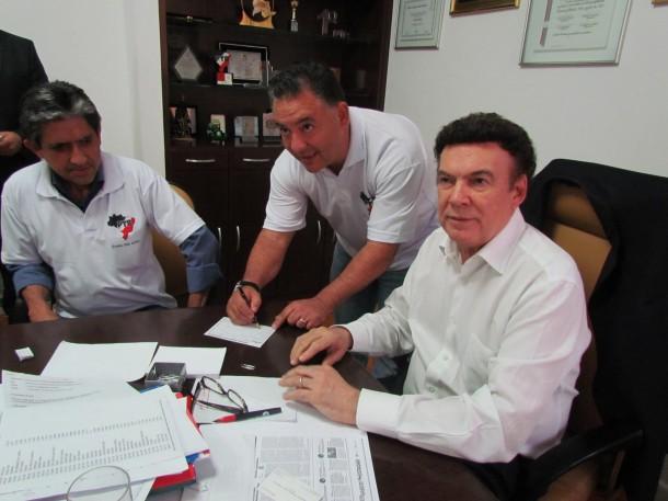 Natinha assina a ficha de filiação do PTB. Ao lado, o vereador Gilvan da Saúde e o presidente estadual da sigla Campos Machado. (Foto: Reprodução)
