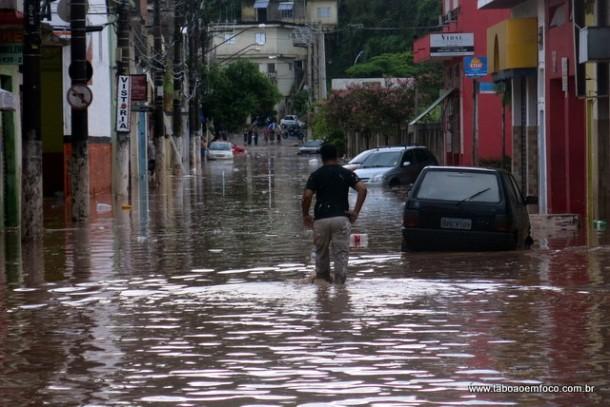 Homem caminha em rua alagada no Centro de Taboão da Serra.