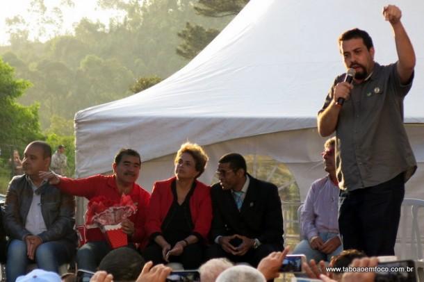 Líder do MTST, Guilherme Boulos, discursa em Taboão. Ao fundo, Dilma fica ao lado do líder do MST, Paulo Félix.