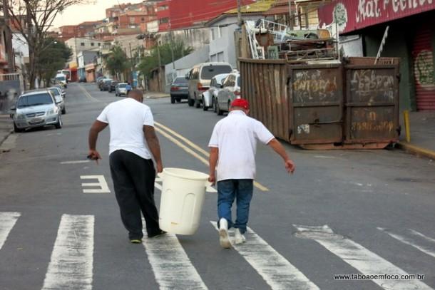 Homens carregam balde de agua em Taboao