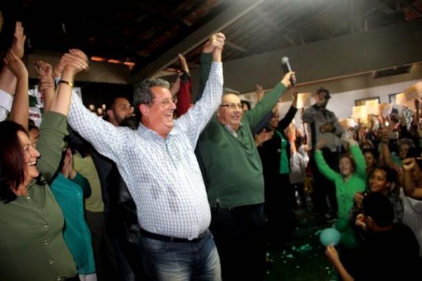 Buscarini (verde) segura a mão do seu candidato a vice Paulo Silas durante convenção do PV. (Foto: Divulgação)