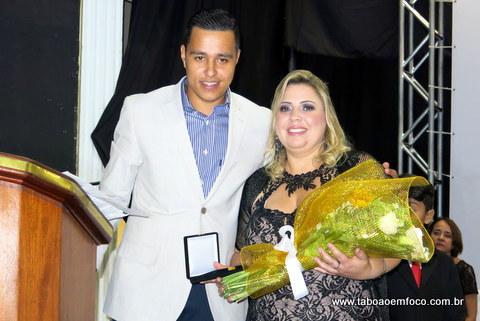 Eliana recebe medalha comemorativa e flores do vereador Johnatan Noventa.