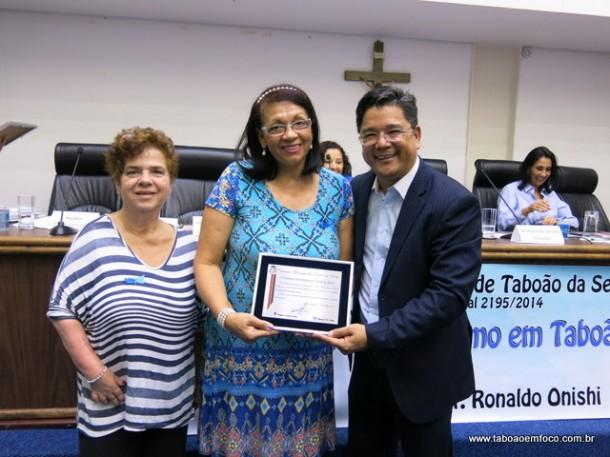 A secretária de saúde, Raquel Zaicaner, a ativista Pró-Autista Ana Ruiz e o vereador Ronaldo Onishi durante entrega de homenagem durante Encontro de Autismo.
