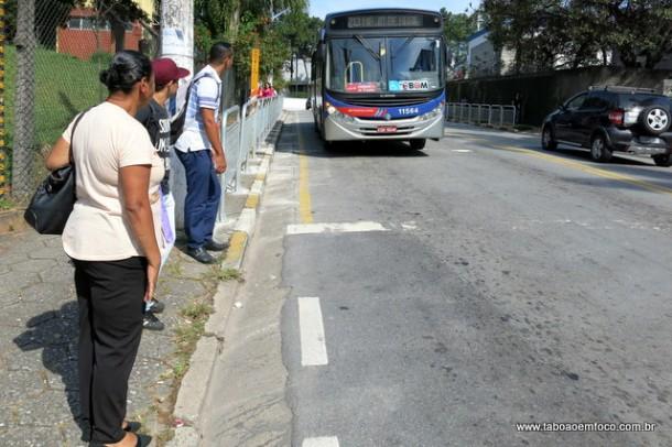 Passageiros esperam ônibus fora do ponto, que foi cercado por grades.
