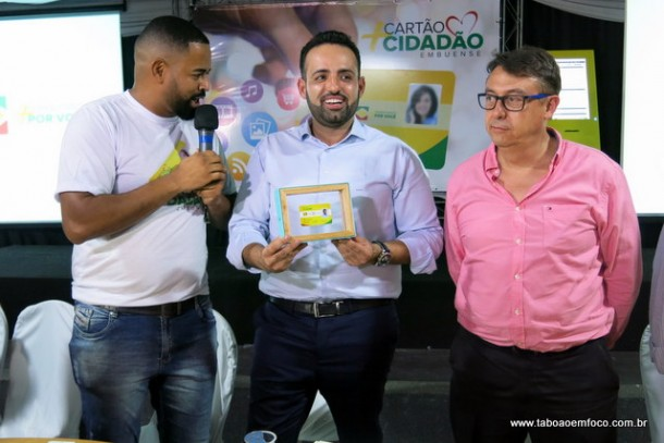 Ney Santos recebe do secretário Jones Donizete o primeiro Cartão Cidadão Embuense. Ao lado, o vice-prefeito Dr. Peter.