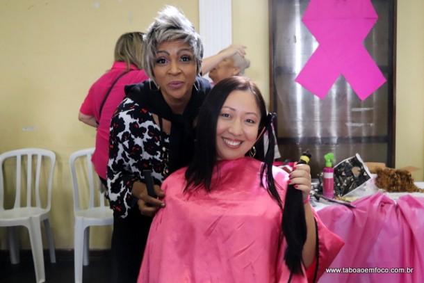 Mulher doa cabelo em evento de abertura do Outubro Rosa.